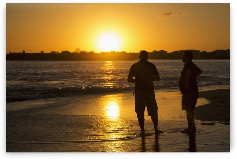 Two men stand in the tide water on a beach at sunset; Caloundra, Queensland, Australia by PacificStock