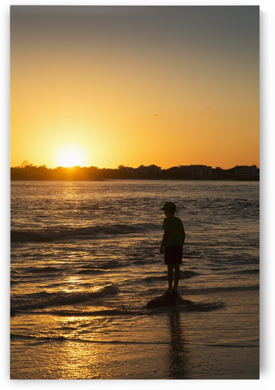 Silhouette of a young boy standing at the water's edge at sunset; Caloundra, Queensland, Australia by PacificStock