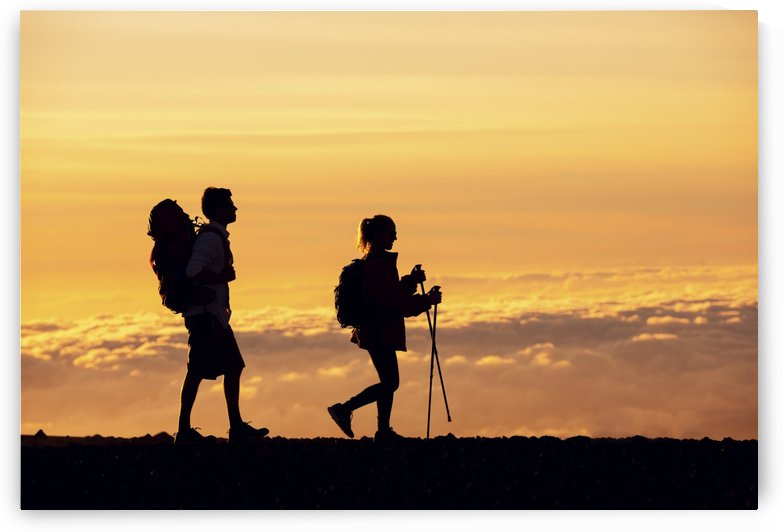 Silhouettes of two hikers with backpacks walking at sunset. Trekking and enjoying the sunset view from mountain top above the clouds. by PacificStock