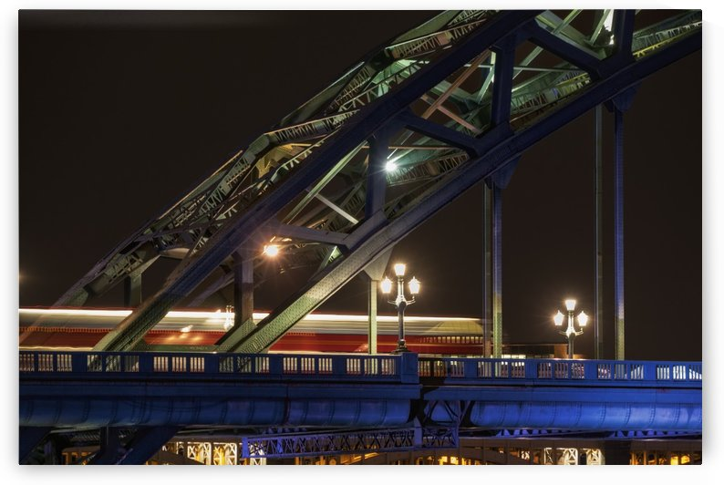 Close up of the illuminated arch of a bridge and lamp posts at nighttime by PacificStock