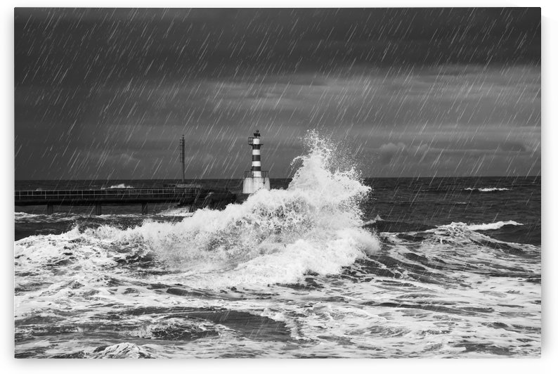 Rainfall and splashing waves with a lighthouse along the coast; Amble, Northumberland, England by PacificStock