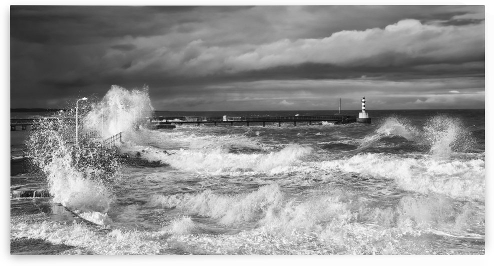 Waves crashing along the coast with a small lighthouse at the end of a pier; Amble, Northumberland, England by PacificStock