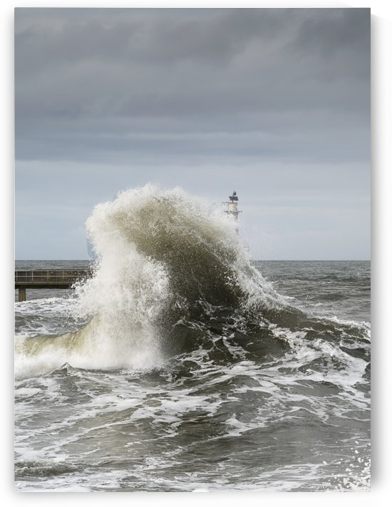 Large wave crashing at the coast with a lighthouse at the end of a pier; Amble, Northumberland, England by PacificStock