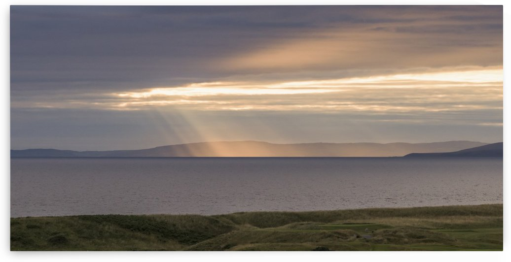 Sunlight shining through clouds onto the coastline; Turnery, Scotland by PacificStock