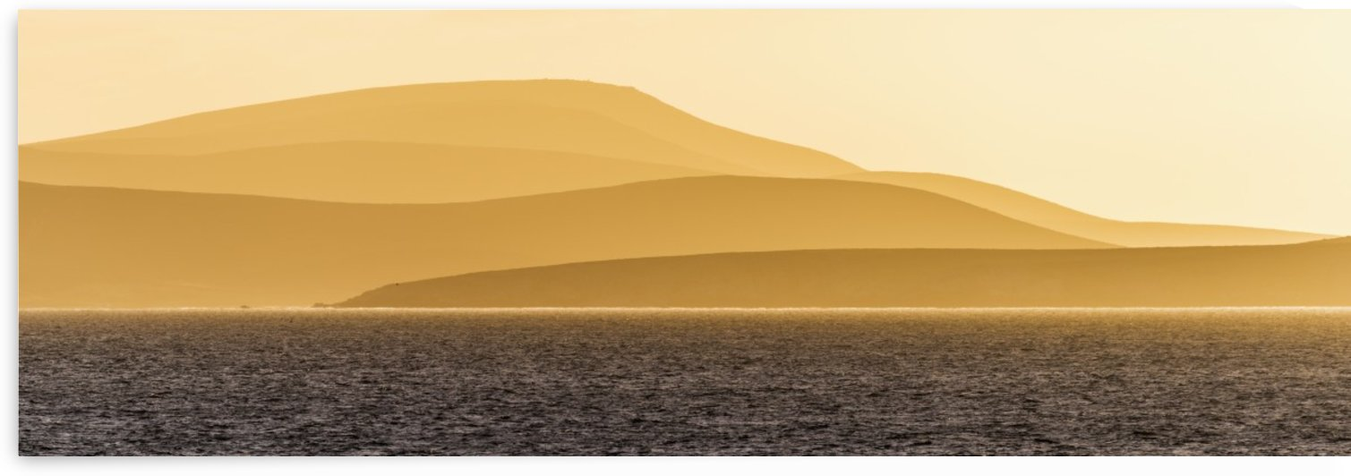 Sunrise over orange hills and blue ocean; Antarctica by PacificStock