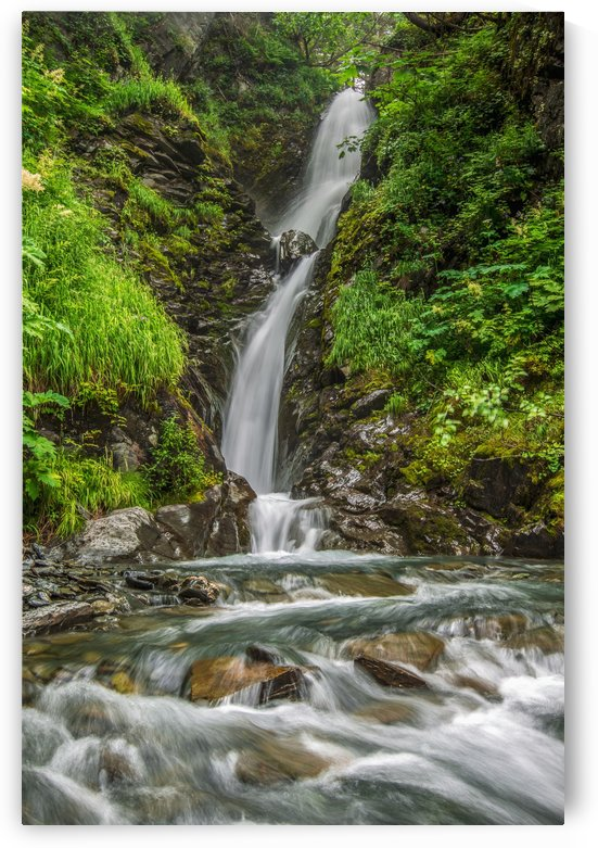 An unnamed waterfall flows down a series of drops in the mountains near Valdez; Alaska, United States of America by PacificStock