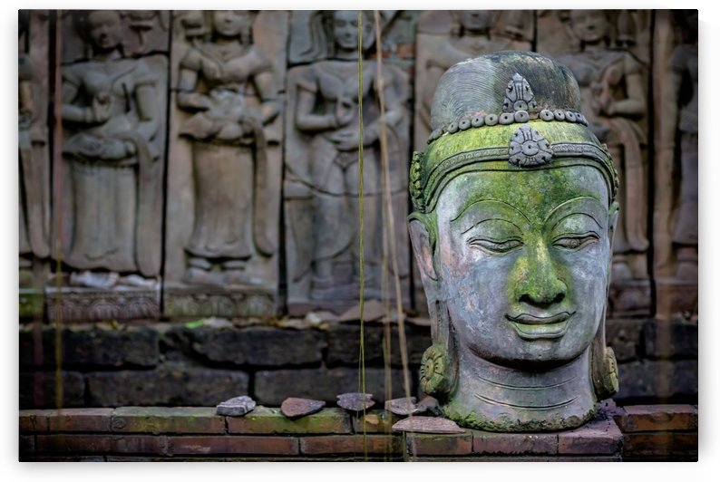 A terra cotta head of buddha sits in front of bas-relief in a terra cotta garden; Chiang Mai, Thailand by PacificStock