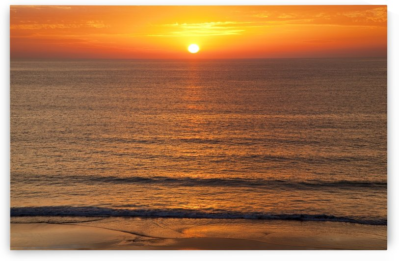 A golden sun sinking into the horizon over the ocean; Andalusia, Spain by PacificStock