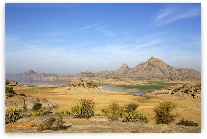 Dramatic Rajasthani dessert landscape with lake and Aravali Hill views by PacificStock