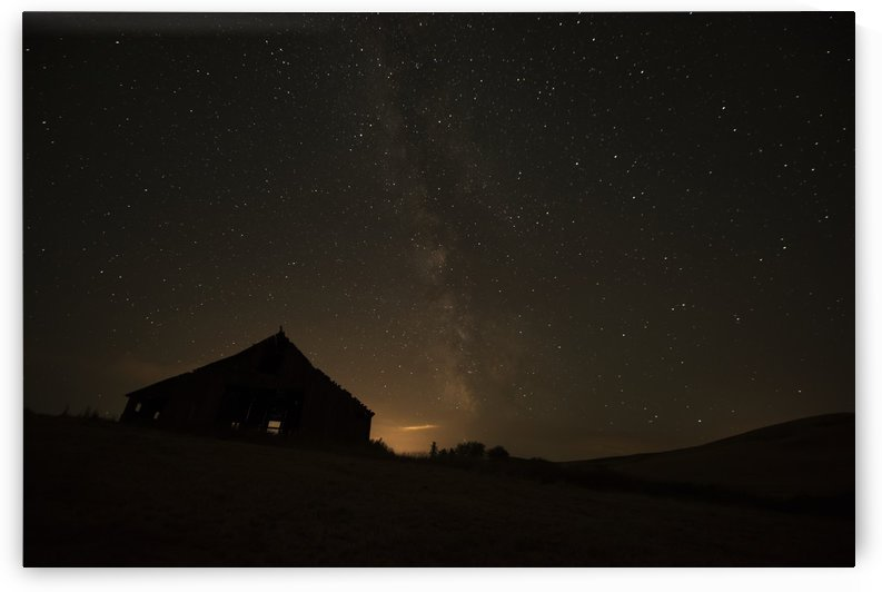 Night sky glowing over silhouette of a barn with a peaked roofline; Palouse, Washington, United States of America by PacificStock