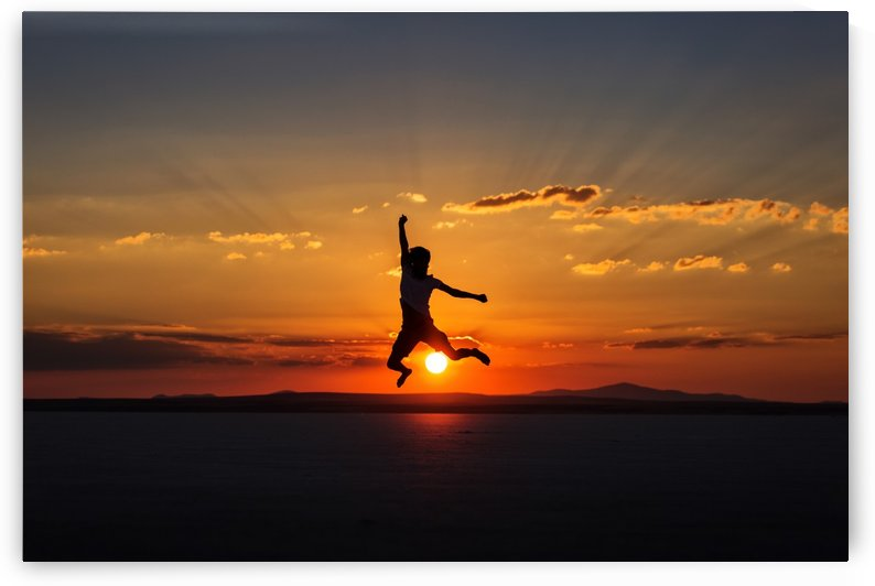 Man jumping with joy at sunset by MIRICA DAN-ALEXANDRU