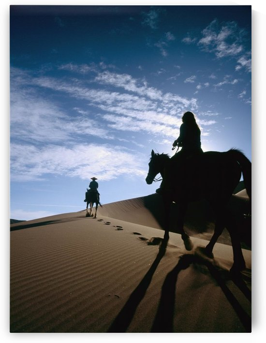 Horseback Riders In Silhouette On Sand Dune by PacificStock