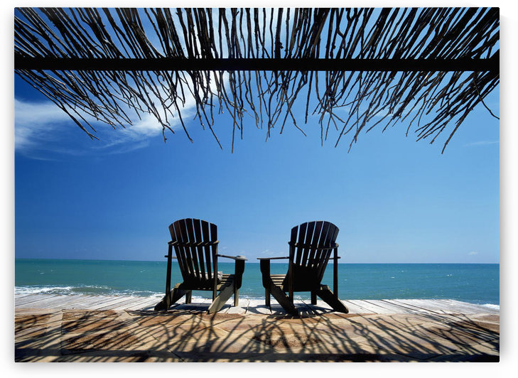 Two Chairs On Deck By Ocean Shaded By Grass Roof by PacificStock