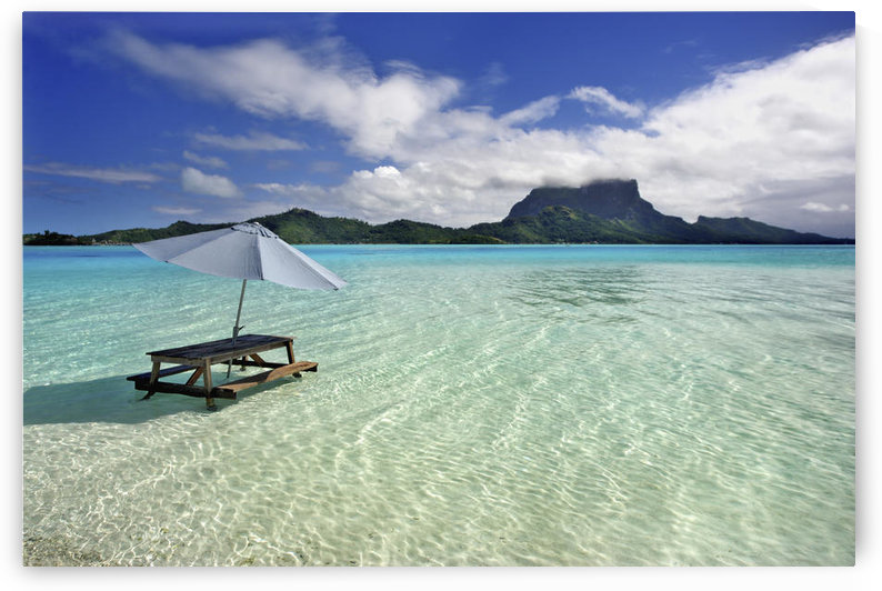 French Polynesia, Tahiti, Bora Bora, Picnic Table And Umbrella In Clear Lagoon Water. by PacificStock