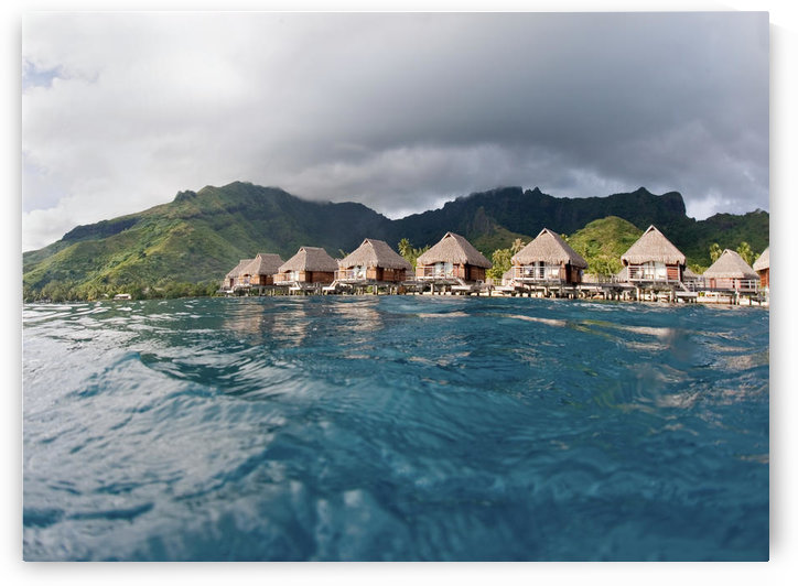 French Polynesia, Moorea Lagoon Resort, Bungalows Over Beautiful Turquoise Ocean. by PacificStock