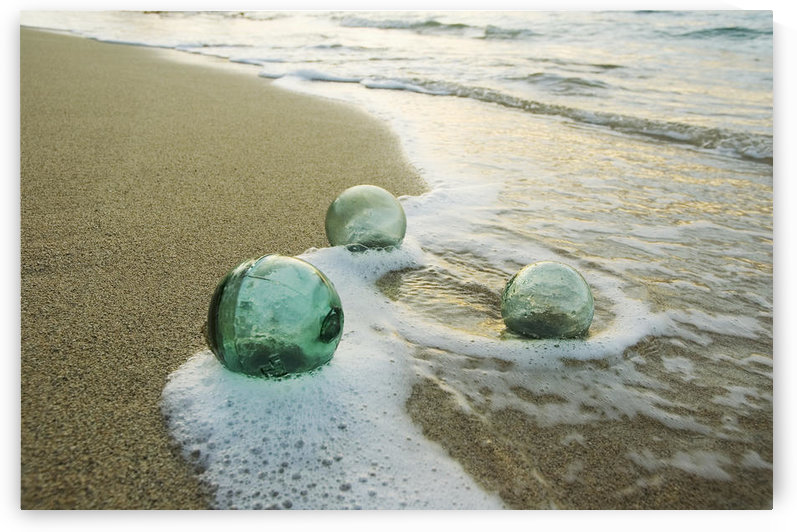 Three Glass Fishing Floats Roll On The Sandy Shoreline With Ripples Of Water And Seafoam by PacificStock