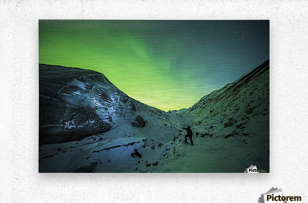 A man lights up the ice of Castner Glacier with a flashlight underneath a diffuse aurora display; Alaska, United States of America  Metal print