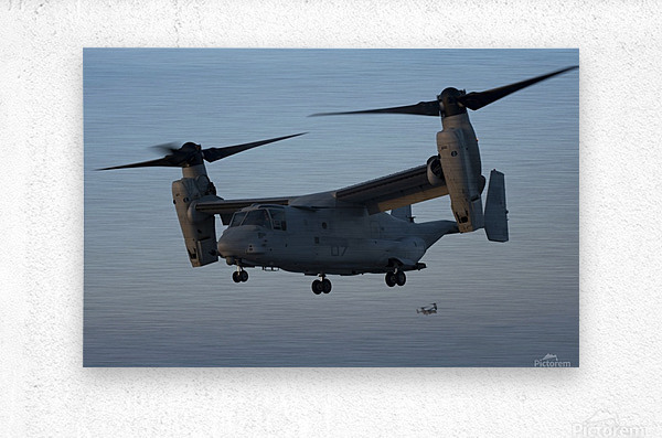 An MV-22 Osprey prepares to land on the flight deck of USS Anchorage.  Metal print