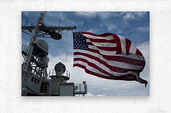 USS Cowpens flies a large American flag during a live fire weapons shoot.  Metal print