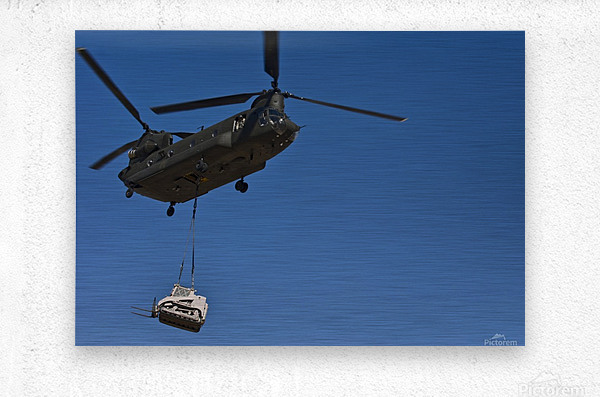 A U.S. Army CH-47 Chinook carries a bulldozer to a drop site.  Metal print