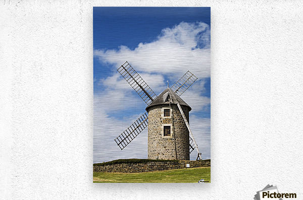 An old stone windmill on a hillside with wooden blades, surrounded by a stone fence with blue sky and clouds; Brehec, Brittany, France  Metal print