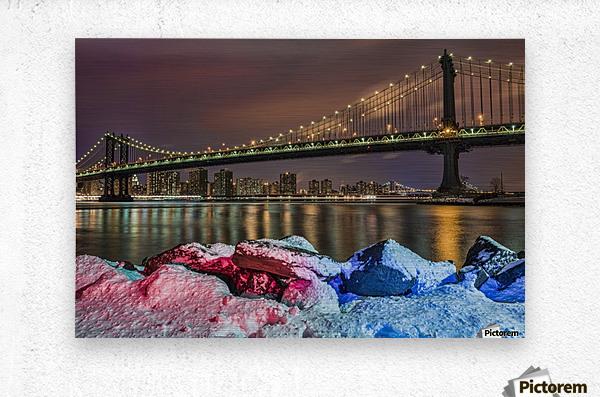Manhattan Bridge by snow-covered rocks at sunset, Brooklyn Bridge Park; Brooklyn, New York, United States of America  Metal print
