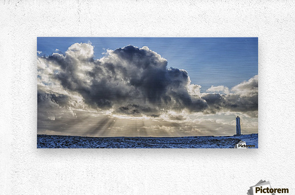 Rays of light shine out from behind the clouds in the skies above a lightnouse along the southern shore of Iceland; Iceland  Metal print
