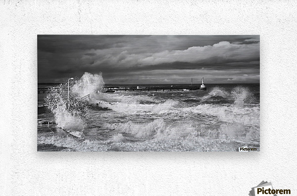 Waves crashing along the coast with a small lighthouse at the end of a pier; Amble, Northumberland, England  Metal print