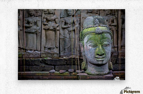 A terra cotta head of buddha sits in front of bas-relief in a terra cotta garden; Chiang Mai, Thailand  Metal print