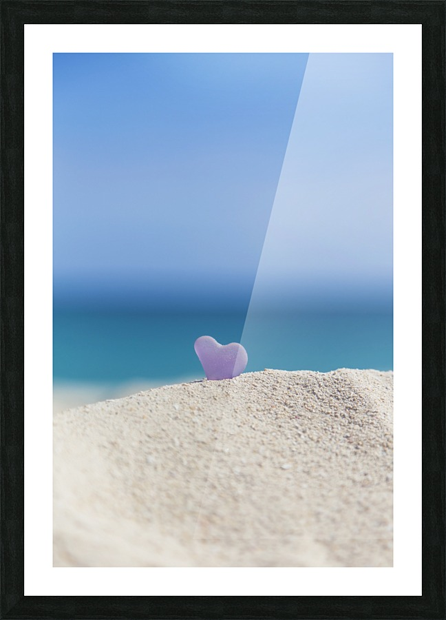 A lavender heart shaped sea glass in the sand at the beach; Honolulu ...