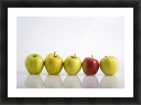 Four Yellow Apples With One Red Apple In A Row On A Reflective Surface; Calgary, Alberta, Canada Picture Frame print