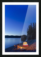 A campfire built on a beach at dusk next to a glowing tent, tranquil ocean water reflecting the warm light, Hesketh Island; Homer, Alaska, United States of America  Picture Frame print