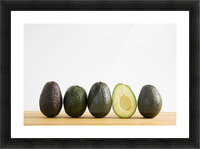 A Row Of Avocados Standing Upright On A Wooden Board With One Cut In Half Without The Pit; Calgary, Alberta, Canada Picture Frame print