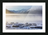 The sun shines through low altitude fog cast in warm light along Turnagain Arm and the Seward Highway, sea ice covering the ocean in the foreground, the Kenai Moutains revealed in the background, South-central Alaska; Alaska, United States of America Picture Frame print