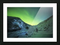 A man lights up the ice of Castner Glacier with a flashlight underneath a diffuse aurora display; Alaska, United States of America Picture Frame print