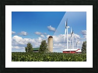 Large metal windmills in a farm yard with red barn and silo, soy bean field in the foreground and blue sky and clouds in the background; Ontario, Canada Picture Frame print