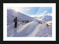 A backcountry skier looks over the Black Rapids Glacier valley from a high point on the terminal moraine in winter; Alaska, United States of America Picture Frame print