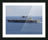 An MH-60S Seahawk helicopter flies over USS George H.W. Bush. Picture Frame print
