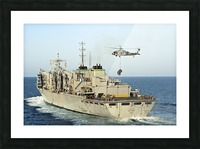 An MH-60S Knighthawk lifts cargo from the fast combat support ship USNS Rainier. Picture Frame print