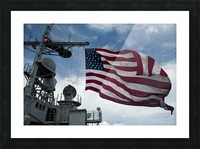 USS Cowpens flies a large American flag during a live fire weapons shoot. Picture Frame print