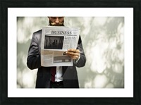 A bearded man reading the business section of a newspaper Picture Frame print