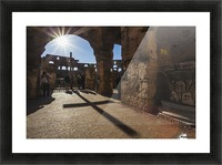 Sunburst through an archway at the Colosseum and a shadow of a cross; Rome, Italy Picture Frame print