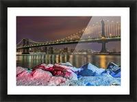 Manhattan Bridge by snow-covered rocks at sunset, Brooklyn Bridge Park; Brooklyn, New York, United States of America Picture Frame print