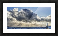 Rays of light shine out from behind the clouds in the skies above a lightnouse along the southern shore of Iceland; Iceland Picture Frame print