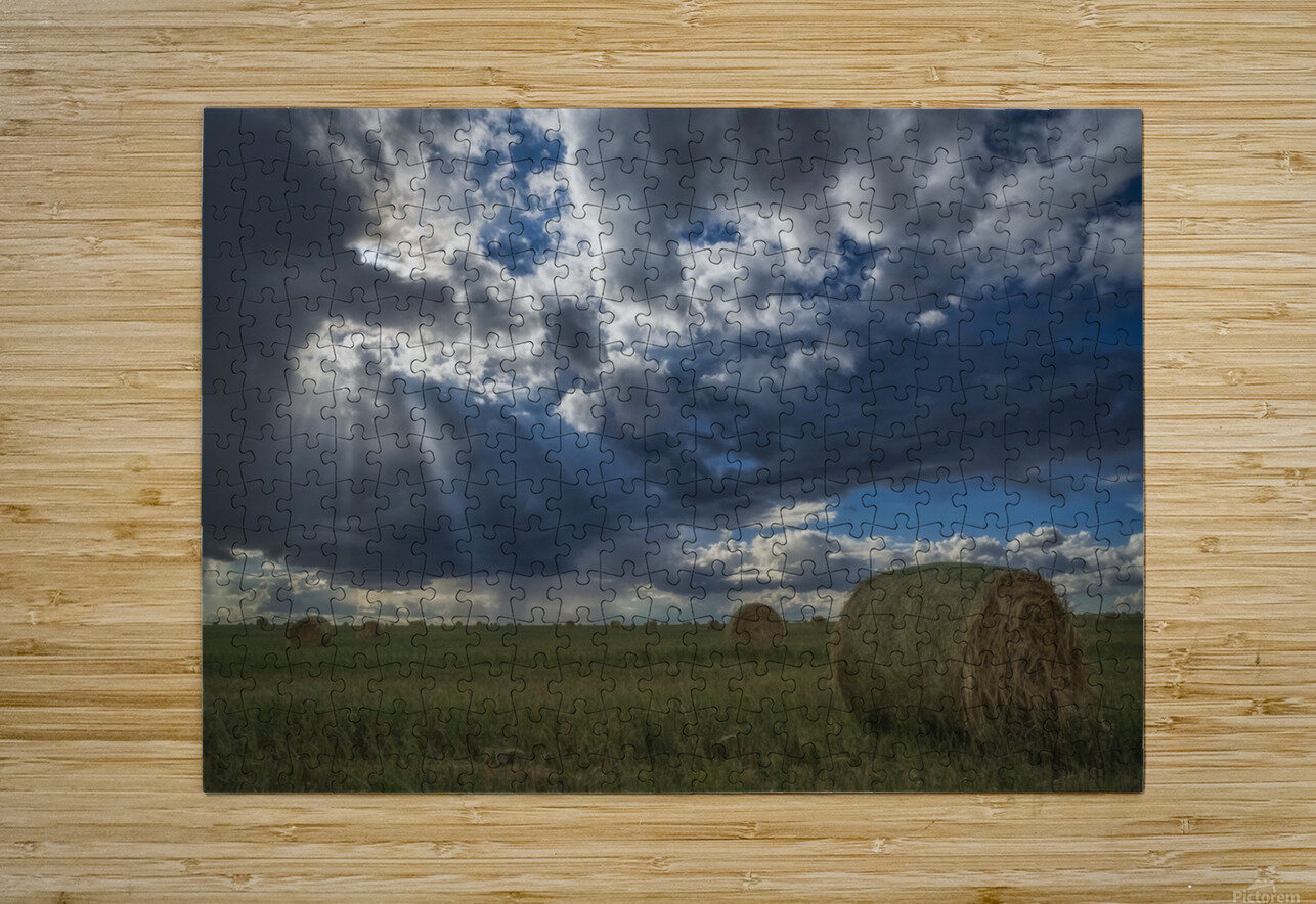 Sunlight breaks through the storm clouds over a field of hay bales; Saskatchewan, Canada  HD Metal print with Floating Frame on Back