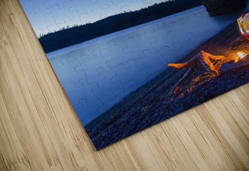 A campfire built on a beach at dusk next to a glowing tent, tranquil ocean water reflecting the warm light, Hesketh Island; Homer, Alaska, United States of America  jigsaw puzzle