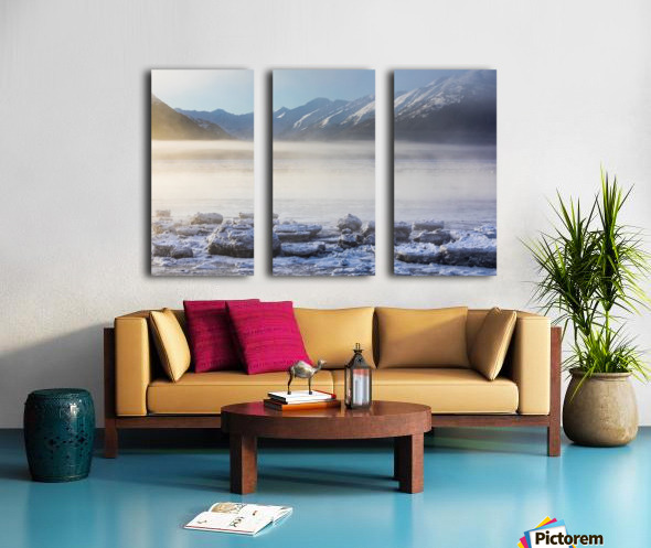 The sun shines through low altitude fog cast in warm light along Turnagain Arm and the Seward Highway, sea ice covering the ocean in the foreground, the Kenai Moutains revealed in the background, South-central Alaska; Alaska, United States of America Split Canvas print