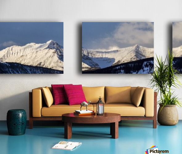 Panorama of snow covered mountains with early morning light, silhouetted forest in the foreground, blue sky and clouds; Kananaskis Country, Alberta, Canada Split Canvas print