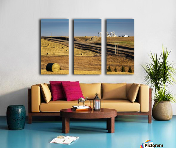 Two pump jacks on rolling hills in the distance along highway with cut fields and hay bales; Alberta, Canada Split Canvas print