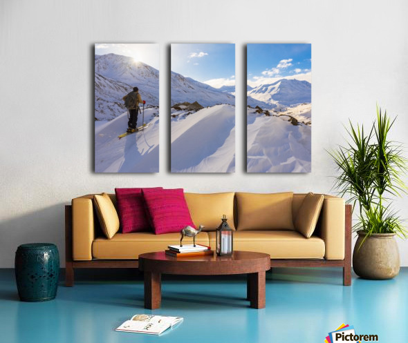 A backcountry skier looks over the Black Rapids Glacier valley from a high point on the terminal moraine in winter; Alaska, United States of America Split Canvas print
